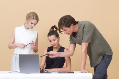 Image of two adults helping one student on laptop