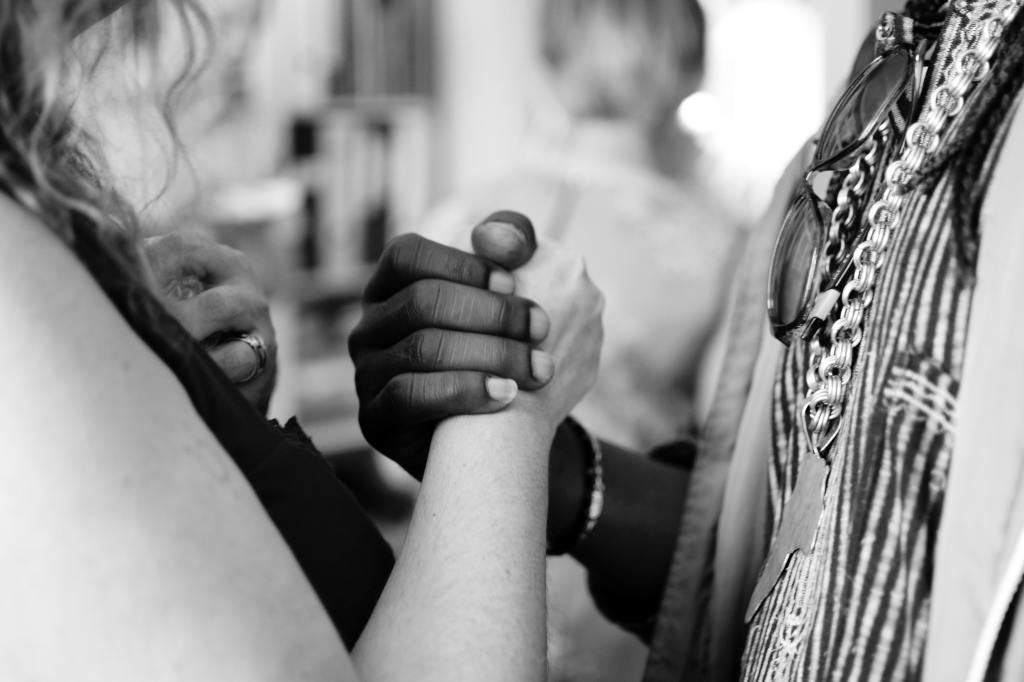 A Black person and a White person holding hands.