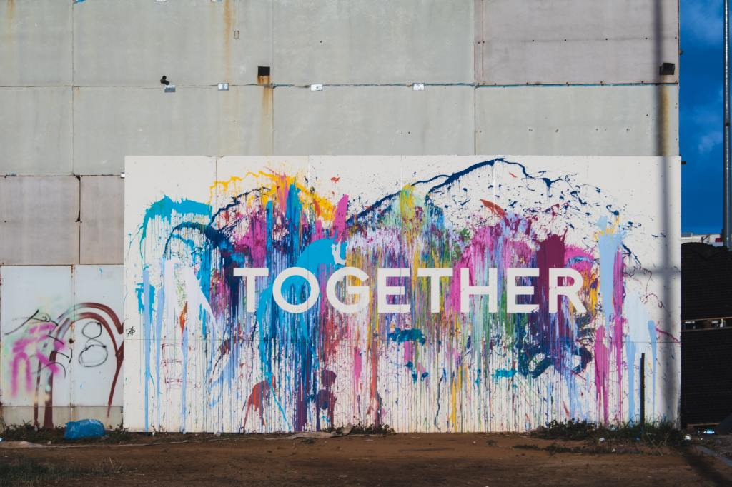 """A billboard with rainbow paint and the word """"together."""""""