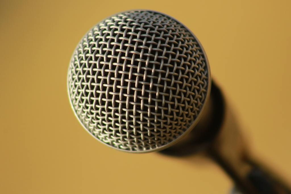 A microphone on a yellow background, facing you.