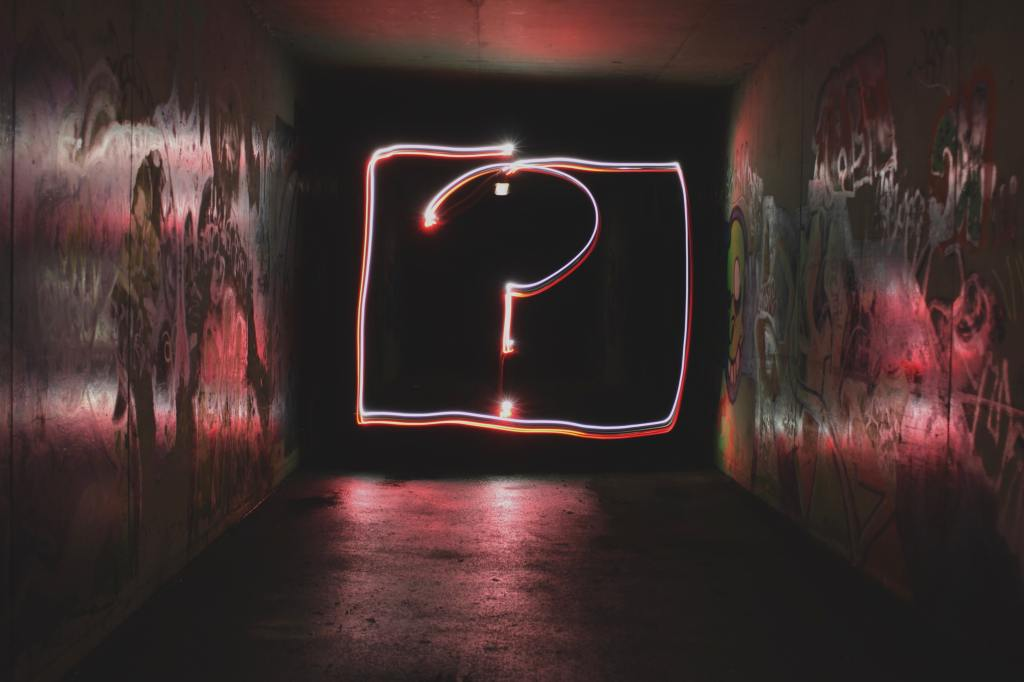 A glowing question mark against a black wall.
