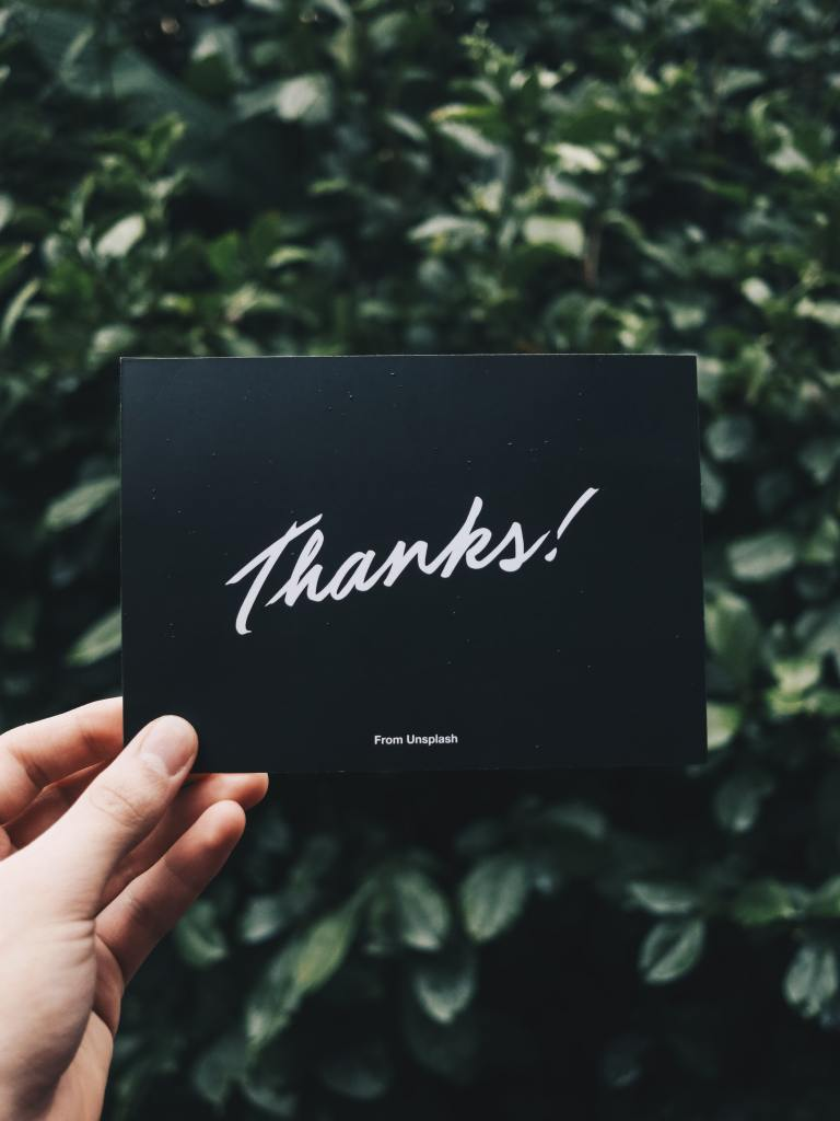 """A person holding a black card that says """"thanks"""" in white letters."""