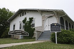 A white two- or three-story building house with green bushes and a paved path. The signs label the house as the Susan LaFlesche Picotte Center and the Susan LaFlesche Picotte Memorial Hospital.