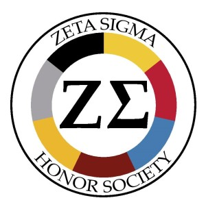 """A round logo. Around the outside are the words """"Zeta Sigma Honor Society."""" In the center are the Greek letters Zeta and Sigma. Between the letters and the name is a ring, divided into segments of black, silver, gold, maroon, blue, red, and yellow, to represent the 9 universities at U.S.G."""