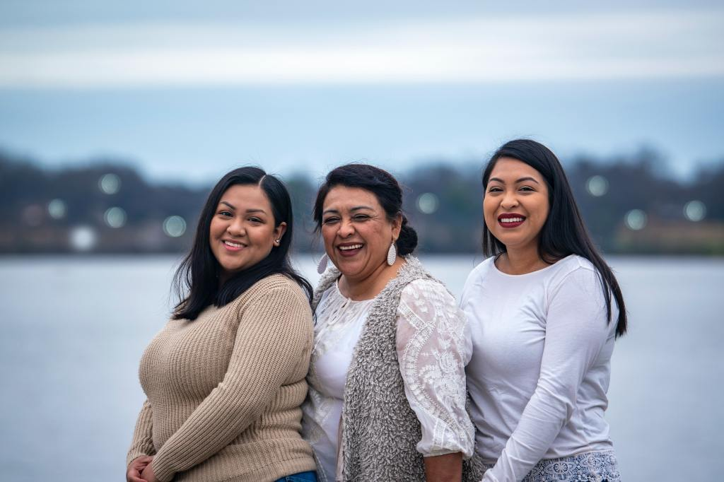 Three Latina women, a mom and her two daughters, smiling.
