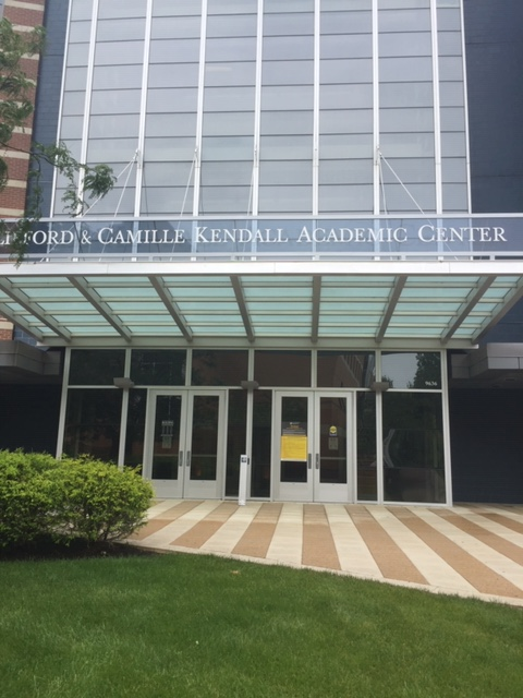 """A modern looking building with lots of windows and a striped concrete entryway. Image Text: """"Clifford and Camille Kendall Academic Center."""""""