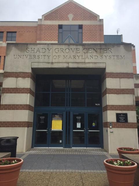 """A building entryway with a blue door and horizontal stripes made of brick. Image Text: """"Shady Grove Center, University of Maryland System."""""""