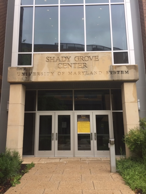 """A yellowish stone entryway. The entry reads, """"Shady Grove Center, University of Maryland System."""""""